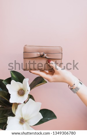 Women's stylish wallet in the hands of a girl with a red manicure on a pink pastel background. A flower in the hand of a girl. The concept of style and fashion. Purse in hand. Сток-фото ©