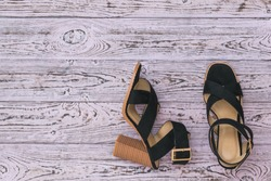 Women's summer shoes of original design on a wooden background. Fashion women's shoes. Flat lay. The view from the top.