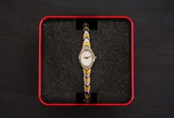 women's watches in a red box on a black background. View from above.