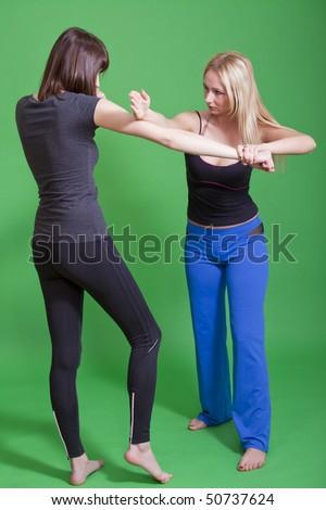 women self defense classes on green background - stock photo
