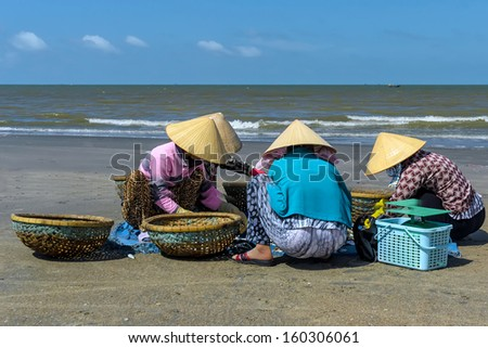 Women selling and buying fish on the beach.