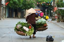 Women selling flowers in the early morning in a small market, Hanoi, Vietnam. Life of florist vendor in Hanoi, Vietnam.