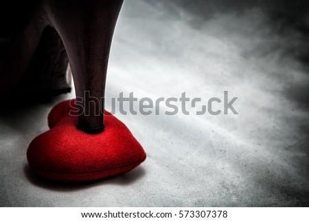 women shoes stomp on broken heart in dark tone., unrequited love., love concept for valentine's day., in dark tone.