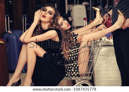 Women shoppers sit in shopping cart, trolley. Women fashion, beauty, look, makeup hair hairstyle #1087435778