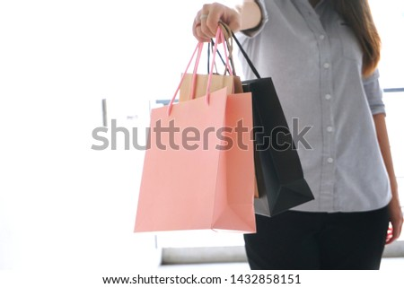 Women show shopping bags with bright background.