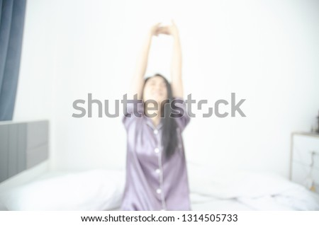 women sit at the edge of the bed. And stretching his arms to relax in the morning.Wake up in the morning. Stretching after waking.Warm tone.Do not focus on the object.Blurred image for background use.