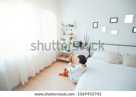 Women sit next to the bed. Look out the window in the morning in the bedroom.