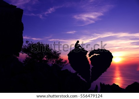 Women sit on broken heart-shaped stone on a mountain with purple sky sunset background.Silhouette Valentine background concept.