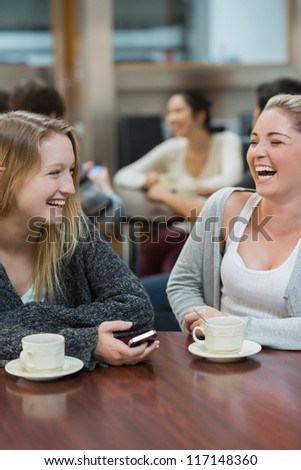 Women sitting at the college coffee shop drinking coffee while laughing