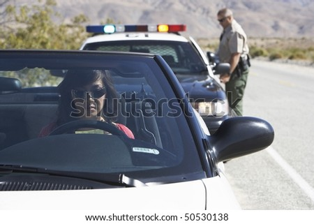 Women sitting in car being pulled over by police officer