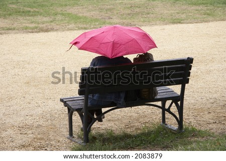 women sitting on a black park bench holding a pink colored umbrella in her hand, rainy day