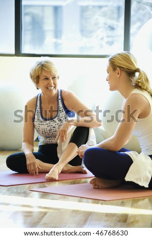 Women sitting on exercise mats and enjoying a conversation at the gym. There are exercise balls behind them. Vertical shot.