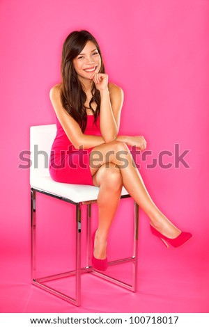 Women sitting portrait on pink. Woman sitting on chair in full length studio portrait on pink background. Beautiful smiling happy Asian Chinese / Caucasian.