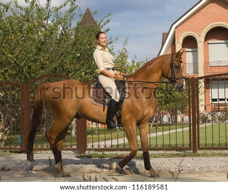 women Smiling riding a brown horse in countryside.