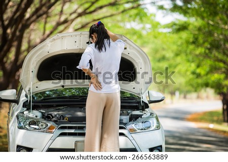 Women spection She opened the hood Broken car on the side See engines that are damaged or not.