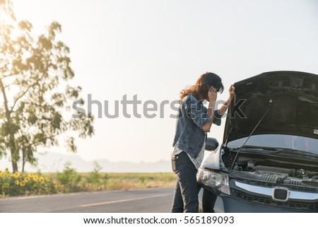 Women spection She opened the hood Broken car on the side See engines that are damaged or not. #565189093