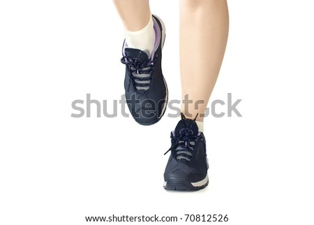 Women sports shoes / sneakers. Closeup of woman legs and feet wearing shoes. Isolated on white background.
