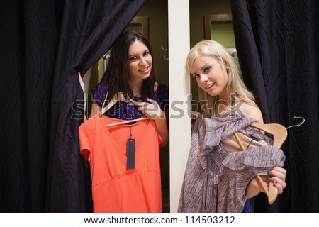 Women stadning in the changing room holding up clothes