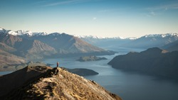 Women standing on the mountain summit enjoying view on lake and mountains during early morning. Shot made during sunrise on Roys Peak summit in Wanaka, New Zealand