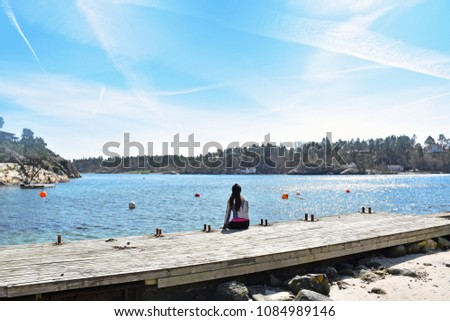 Women stretching on the side of the sea, on the beach after traing. Enjoy the Nice Natural in spring time in the small island at Kongshavnveien, Tromøy island, Arendal City. Norway.