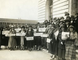 Women Suffragettes holding placards with political activist slogans in 1920. Signs read: Know Your Courts-Study Our Politicians; Liberty in Law; Law Makers Must Not Be Law Breakers; Character in Candi