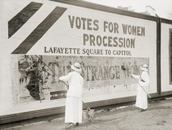Women suffragists cover a billboard to advertise their Washington, D.C. parade. Nation-wide demonstrations were held in May 1914 to support the Federal Amendment enfranchising women.