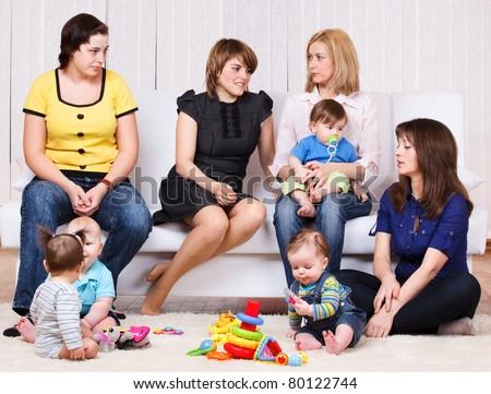 Women talking, their children playing