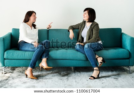 Women talking together on the couch #1100617004