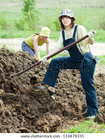 women throws the manure pitchfork in the field