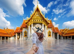 Women tourists holding man's hand and leading him to Wat Benchamabophit or the Marble Temple in Bangkok, Thailand.