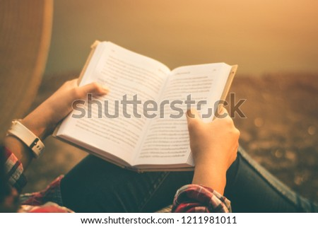 Women tourists read book in quiet nature.