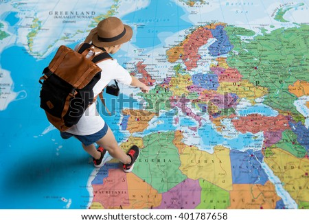 Women traveler Is planning a tour her standing on the world map.she points to the europe