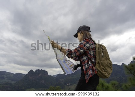 Women traveler with backpack checks map to find directions in wilderness area #590939132