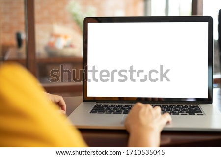 women using laptop computer working at home with blank white desktop screen.