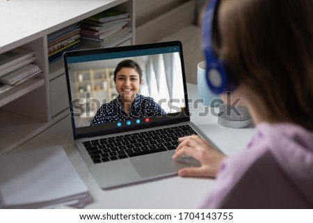 Women via videocall talking using webcam pc internet connection, view over girl shoulder. Indian ethnicity teacher share knowledge with learner. Video Conference application, modern tech usage concept