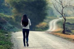 Women walk alone in the fall, the road is empty.
