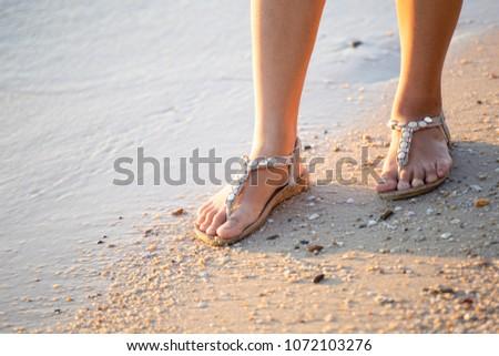 Women walk on the beach in the morning light. #1072103276