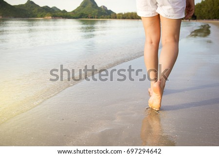 Women walking on the beach with mountain in background.