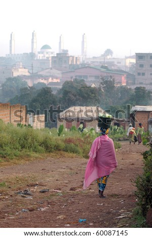 Women walking to the market with goods in Labe with mosque in the background