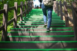 Women walking up the green wooden stairs