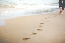 Women was walking a long the beach when evening sunset time.