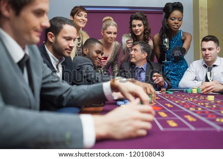 Women watching men play roulette in casino