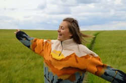 Women waving arms and smiling over the farmers field and crops. Long hair blowing in the wind. Colourful mountaineer sunset jumper. Positive and happy!