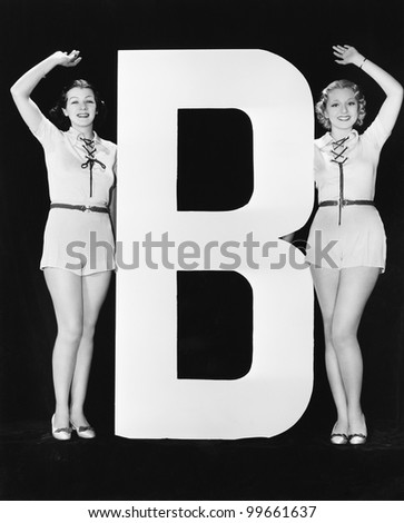Women waving with huge letter B