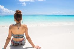 women wear bikini sitting on the beach