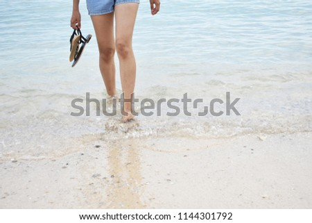 Women wear jeans shorts carrying shoes walking on the beach with clear sea water. #1144301792