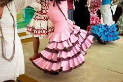 Women wearing flamenco dresses dancing sevillanas at Seville's Feria de Abril.