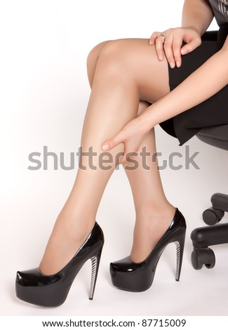 Women wearing high heels black shoes, sitting on the chair and massaging tired legs