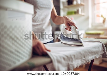 Photo of  Women wearing white shirt ironing clothes on ironing board in laundry room at home