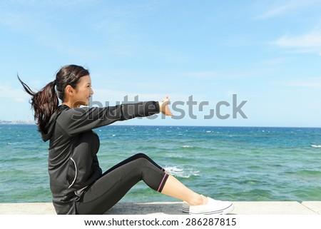 Women who exercises beside the sea